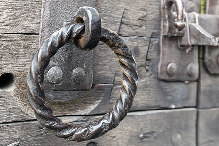 Grungy antique iron door ring on old weathered wooden door.  photo
