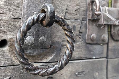 Grungy antique iron door ring on old weathered wooden door.