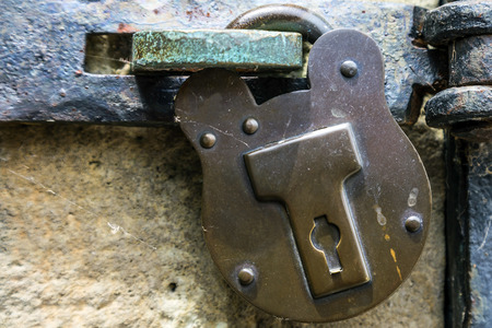 Old fashioned heavy metal padlock with keyhole. Hook and latch on door.