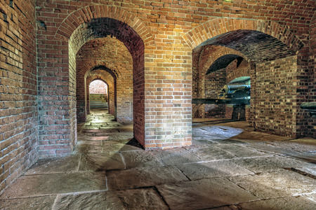 Historic brick archway and tunnel  Antique artillery cannon points out of window
