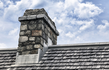 Historic chimney made of cobblestone sits on roof with wooden shingles  Beautiful cloudy background  Stock Photo