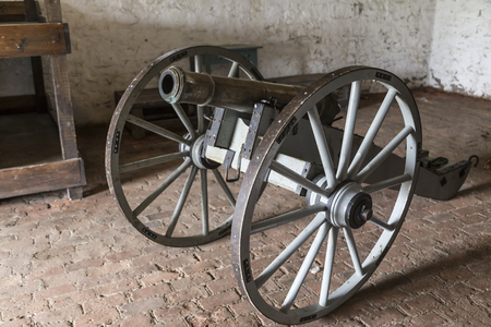 Antique civil war cannon with giant wheels displayed in an old room