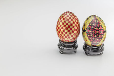 Meticiulously painted eggs with checkers and designs on shiny bases
