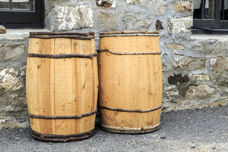 Two wooden hand crafted barrels against cobblestone house  New wood contrasts with old stone