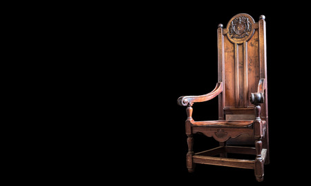 Heavy wooden high backed chair with beautiful scrollwork and craftsmanship  On black background  Stock Photo