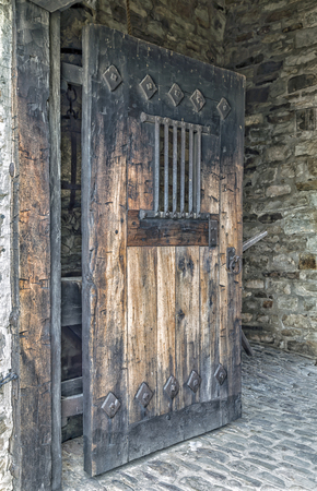 Heavy aged wooden door propped open  There are large iron bars and hinges