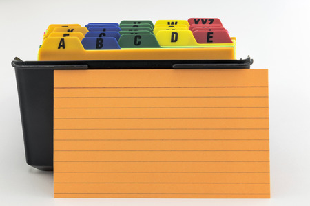 index card: Black plastic box index card filer with colorful alphabetized tabs  Blank orange index card is propped up in front