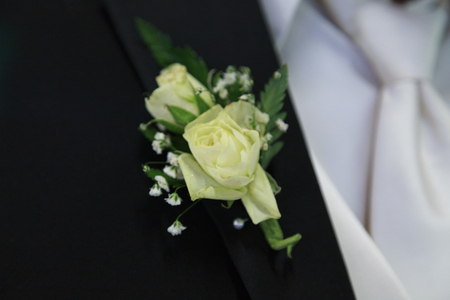 Off white flowers of this grooms boutonniere are pinned to his black lapel.