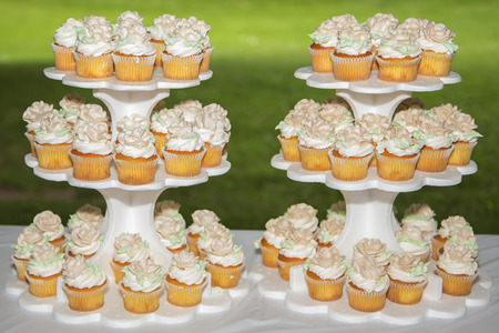Two towers of beautiful delicious cupcakes sit on top picnic table.  Stock Photo