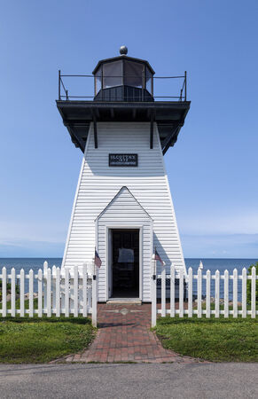 Cute historic and small lighthouse with white picket fence. A brick walk leads to an open door.