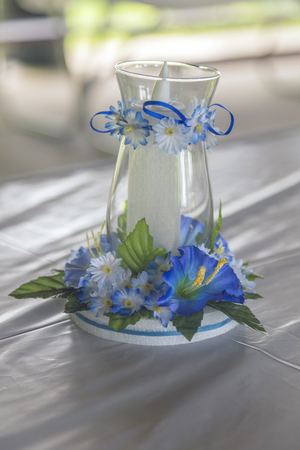 Candle in glass centerpiece. Cute blue flowers and ribbons adorn the glass.
