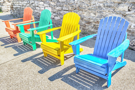 Brightly colored adirondack chairs arranged in a row. Bright sun lights them.
