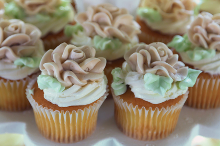 Yummy and delicious buttercream cupcakes with generous amounts of decorative frosting.