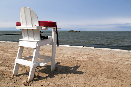 Unmanned white lifeguard chair with floatation device on an empty beach.