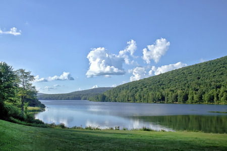 Green mountains surround this placid lake on a blue and clear day in the country. Stock Photo