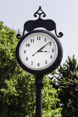 Tall town clock on black pole. Old fashioned minute and hour hands.