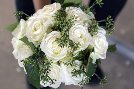 A pretty bouquet of off white wedding roses held for the camera.