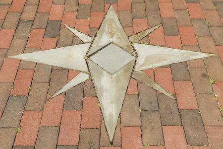 Brick walkway with inlaid eight point star design. Nautical symbol.