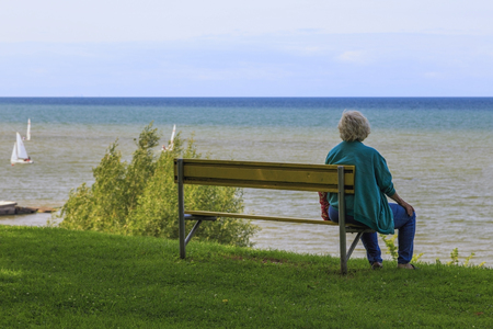 Older woman sits alone on the end of a bench gazing over the harbor.