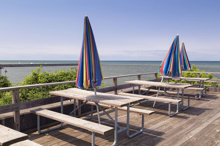 Wooden picnic tables with colorful closed shade umbrellas on a dock over looking the harbor. Stock Photo