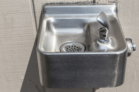 Classic silver metal drinking fountain mounted on the wall.