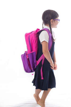 transitional: Young girl is ready to start school in a uniform wearing a backpack.