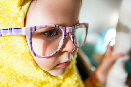 A young girl playing dress up with purple glasses and a yellow bird costume. photo