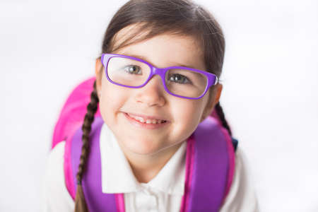 girl glasses: Young girl is ready to start school in a uniform wearing a backpack.