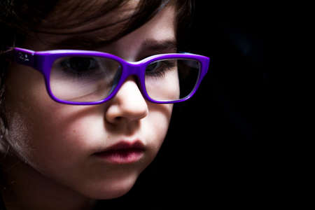A portrait of a young girl with purple glasses and dramatic lighting. photo