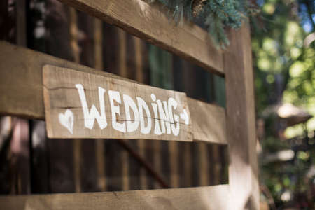 directional arrow: The word wedding is painted a sign with a directional arrow.