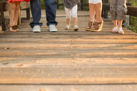 A family with three daughters is standing on a wooden bride with only their feet visable. Stock Photo