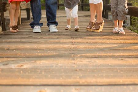 Une famille de trois filles est debout sur une fiancée de bois avec seulement leurs pieds très lisibles. Banque d'images - 37217627
