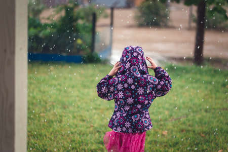 A young girl is feeling hail for the first time.