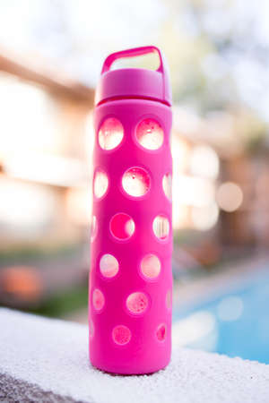 A glass hot pink water bottle is half full of cold water. Stock Photo