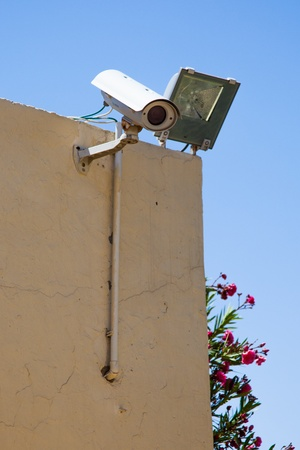 close circuit camera: Video camera of system of supervision on a building wall with light Stock Photo