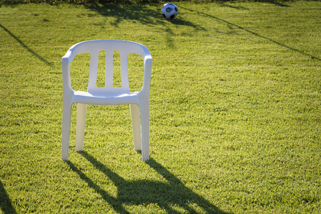 A plastic chair in a meadow photo