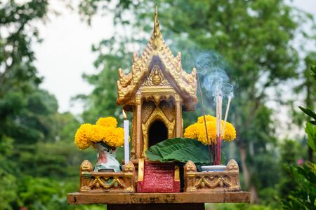joss: joss house in thailand with flowers in vases and some wreathes