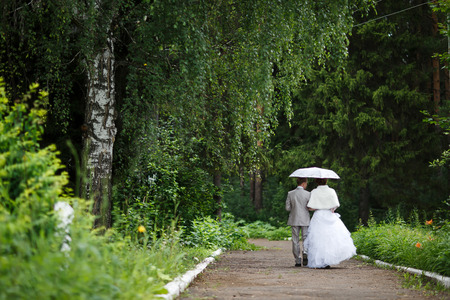 Beautiful just married couple under umbrella walking away on road at park. the bride and groom under an umbrella