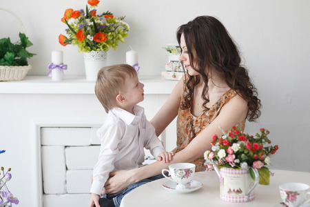 flowers boy: Beautiful blond boy kissing a girl mom in the room with a spring interior Stock Photo