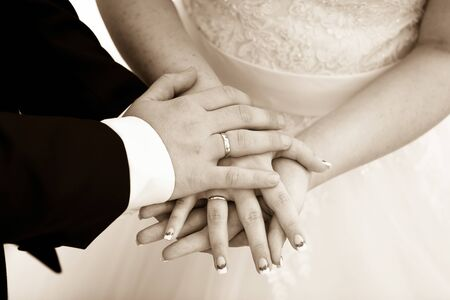 wedlock: Bride and groom holding hands outdoors. Beautiful wedding rings. Stock Photo