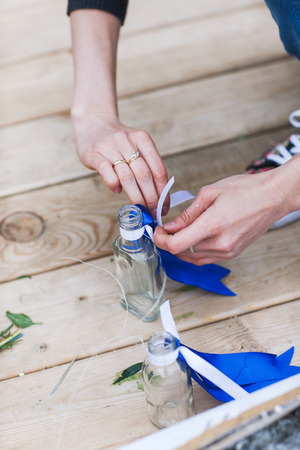 tied girl: The girl hands touching flowers in a small vase. Flowers in the bottle. The girl is tied in a ribbon bow.