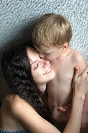 sincere girl: Boy kisses his young mother. Mom smiles and laughs.