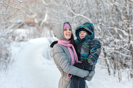 glory of the snow: Beautiful young mother walking with her son in the winter forest.