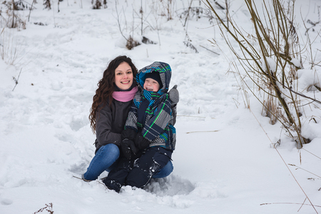 glory of the snow: Happy and cheerful mom and son walk in the winter woods. Stock Photo