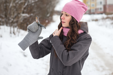 Beautiful young girl looks in the mirror and preens in winter outdoors.