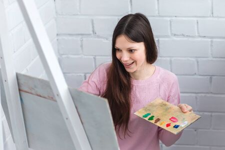 Beautiful young woman painting a picture on an easel. Hold in your hands a brush and palette of paints.