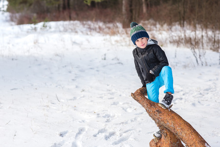 glory of the snow: Beautiful cheerful boy is walking and playing in the winter park.