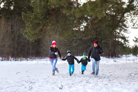 glory of the snow: Happy family walks and playing with snow in winter forest