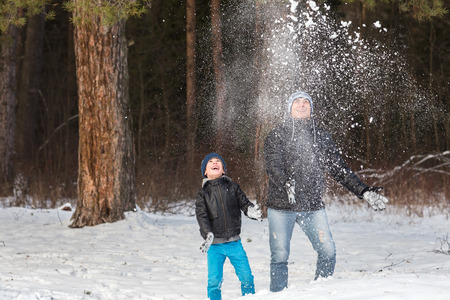fling: Happy dad with his son playing in the winter snow park