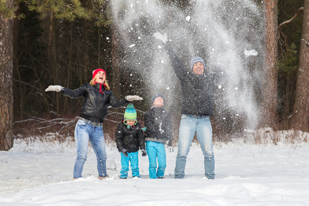 affable: Happy family walks and playing with snow in winter forest